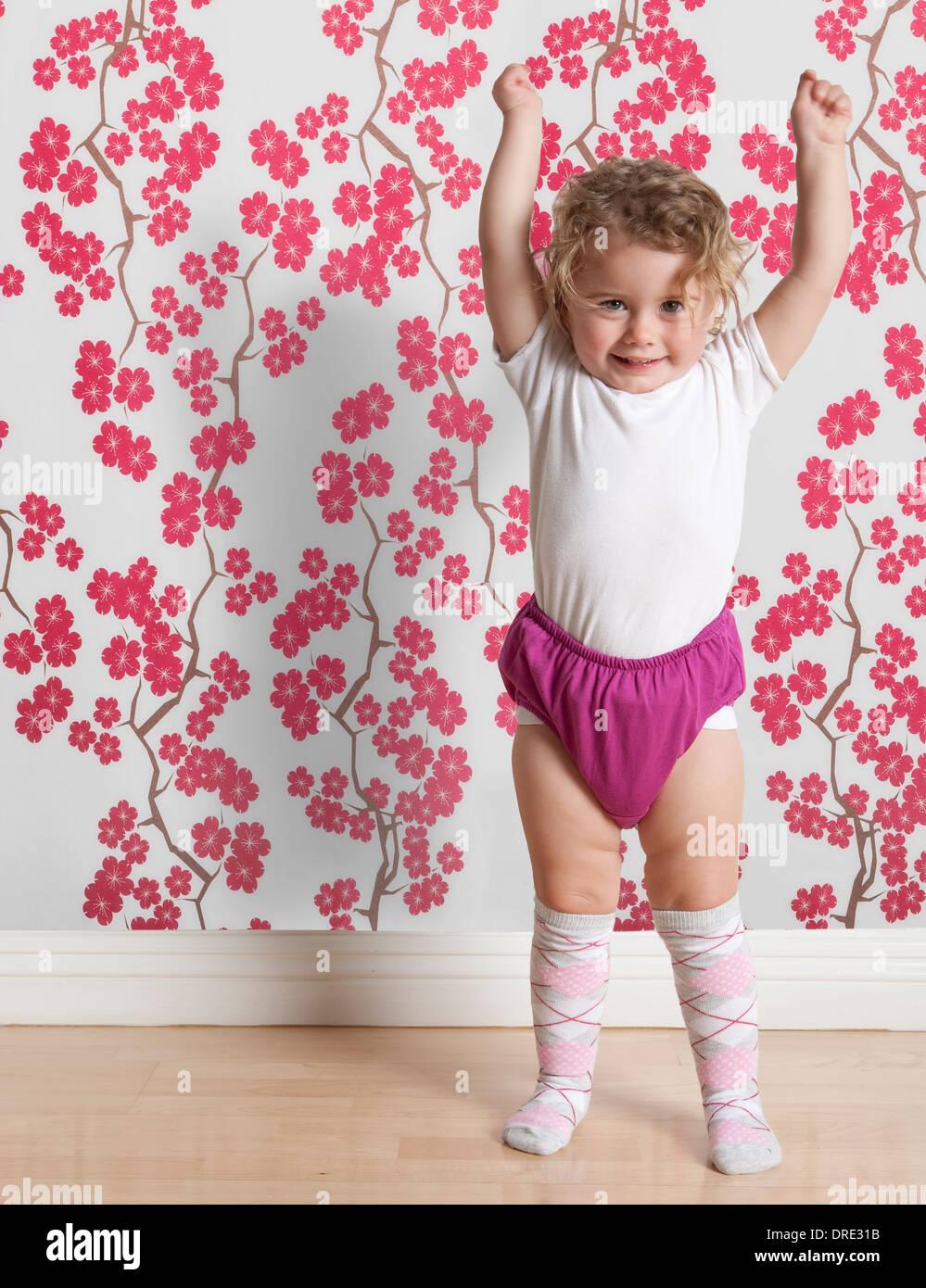 Kleinkind vor bunten Tapeten Stockbild