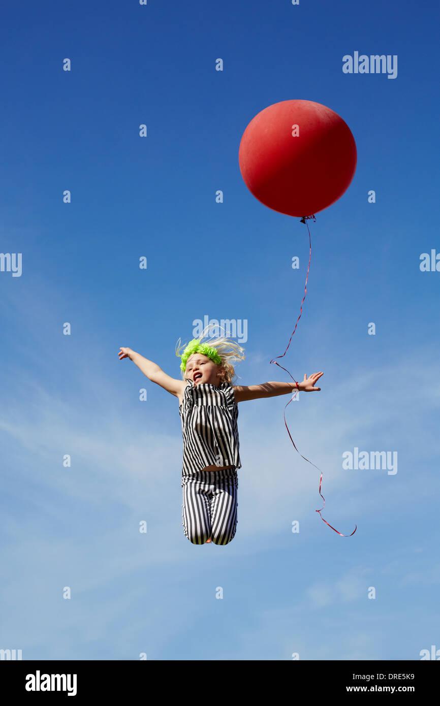 Mädchen mit einem roten Ballon in die Luft springen Stockbild