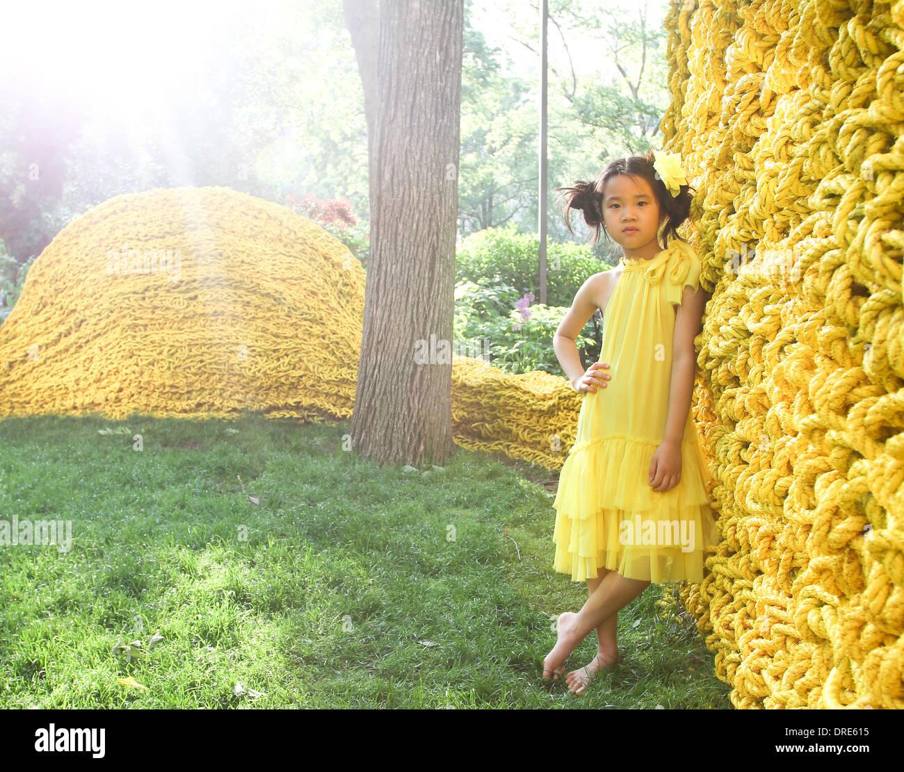 Junge asiatische Mädchen in gelben Kleid in der Nähe von gelbe Wand Stockbild
