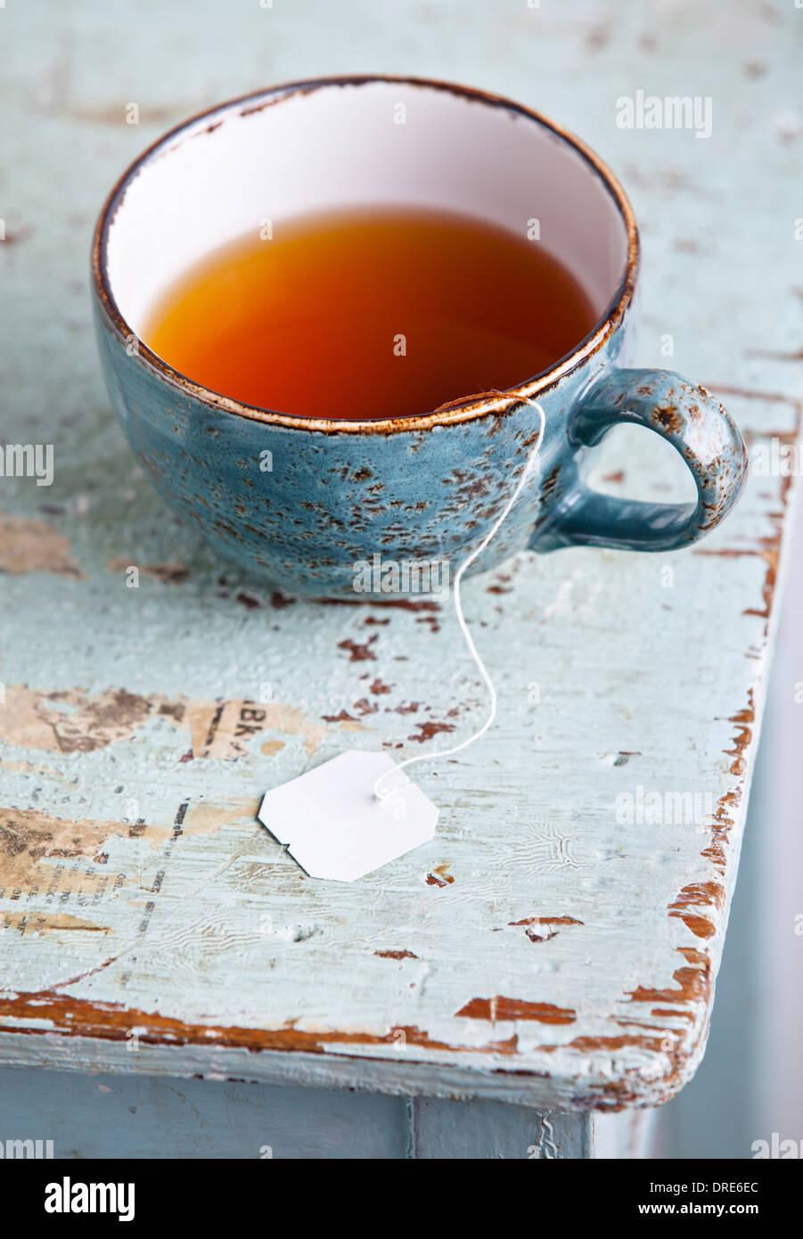Tasse Tee mit Teebeutel auf blauem Hintergrund Textur Stockbild
