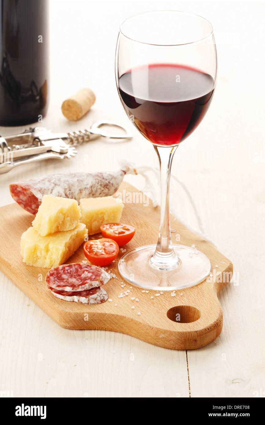 Rotwein und Auswahl an Käse und Snacks auf weißem Hintergrund Stockbild