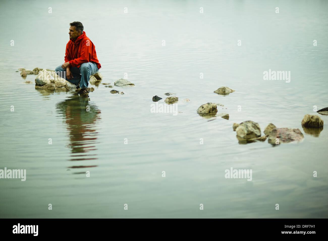 Colorado USA Mann auf stepping stone nachdenkliche Haltung ausgeglichen Stockbild