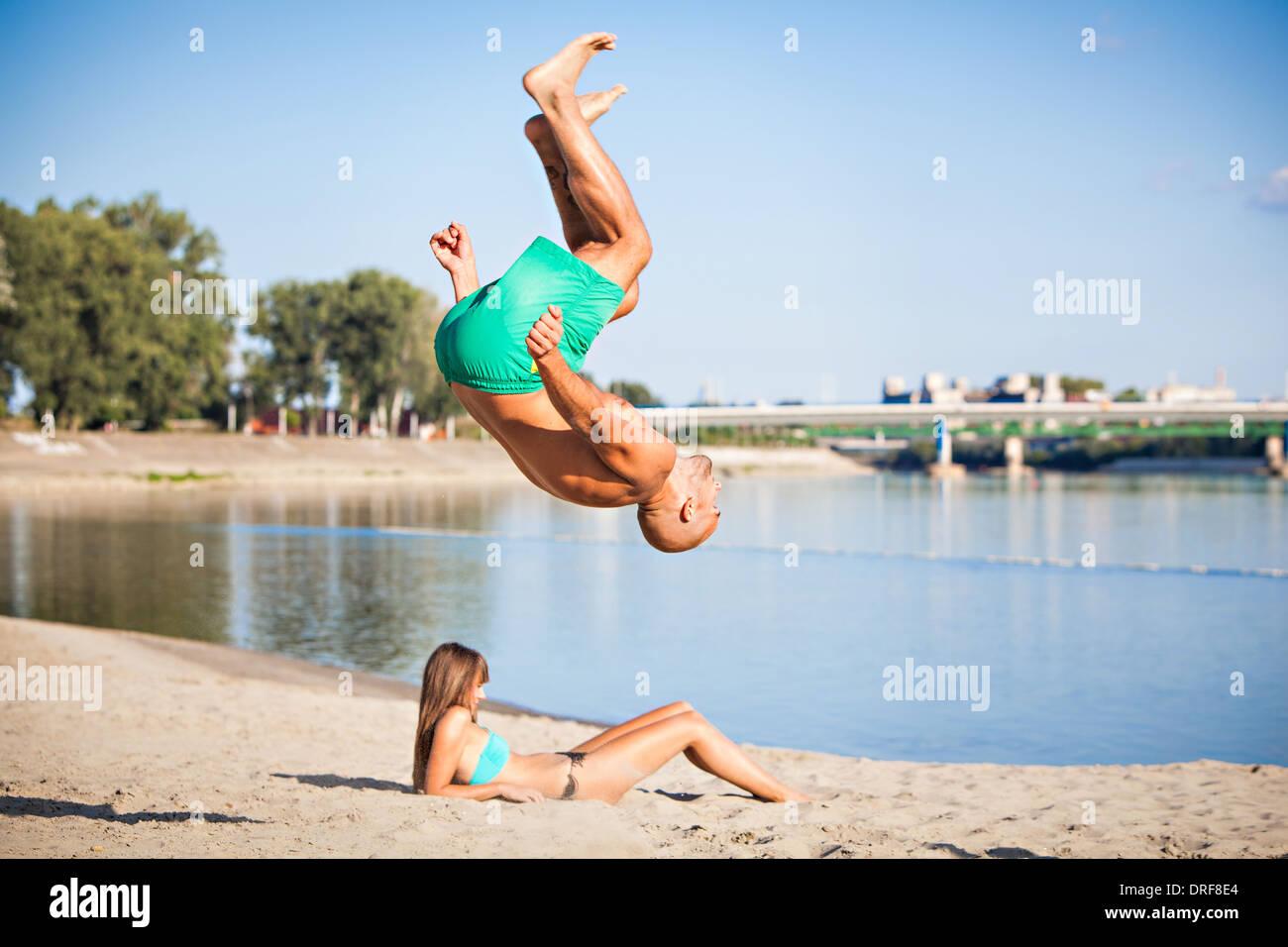 Junger Mann Saltos auf dem Strand, Drau, Osijek, Kroatien Stockbild