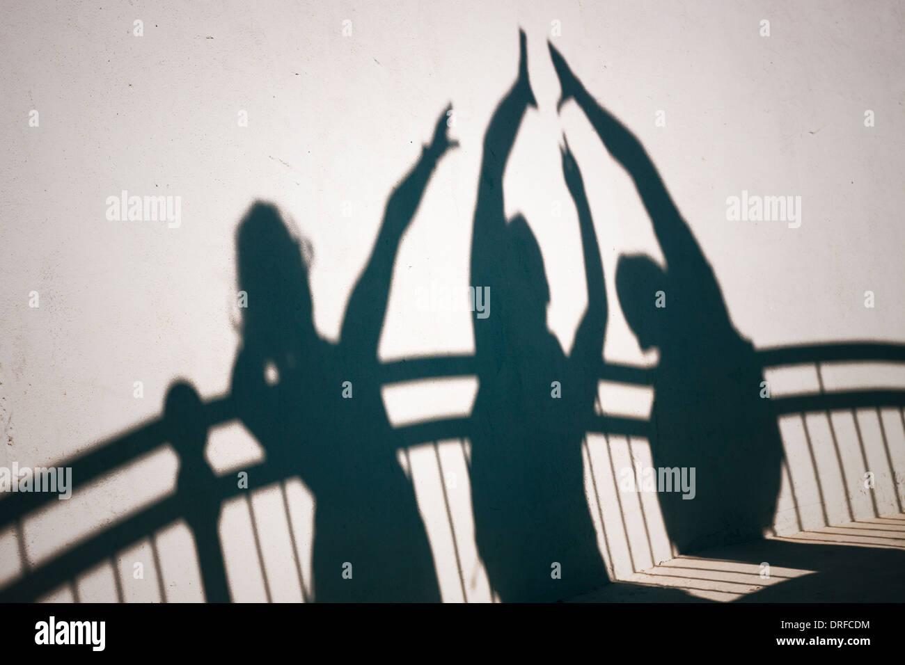 Kreative Fotos von glücklichen Menschen Schatten auf die weiße Wand gestikulieren hoch fünf Stockbild
