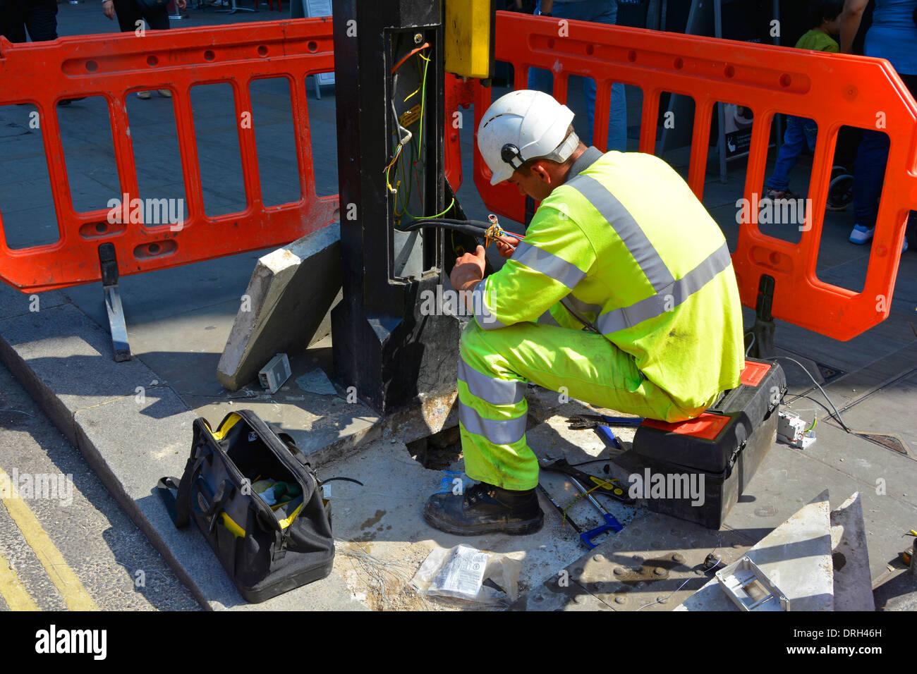 Elektriker arbeiten an Kabeln auf Basis der Straßenbeleuchtung Spalte Stockbild