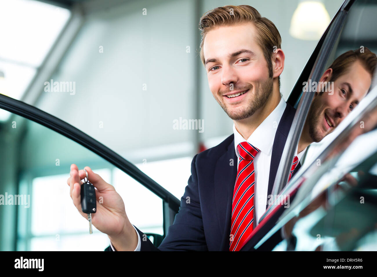 Verkäufer oder Auto Verkäufer im Autohaus mit Schlüssel präsentiert seine neue und gebrauchte Autos im showroom Stockbild
