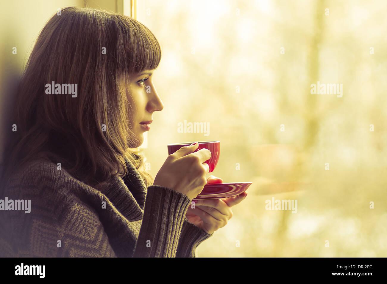 Kaffee. Hübsches Mädchen, trinken Kaffee oder Tee in der Nähe von Fenster. Warme Farben getönt Stockbild