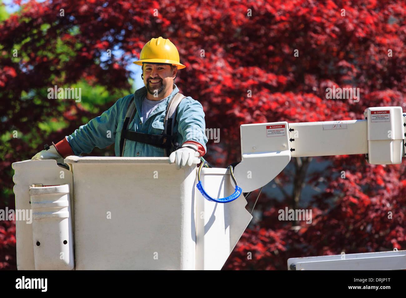 Energie Ingenieur in Eimer tragen einen Sicherheitsgurt zu heben und isolierte Handschuhe, Braintree, Massachusetts, USA Stockbild