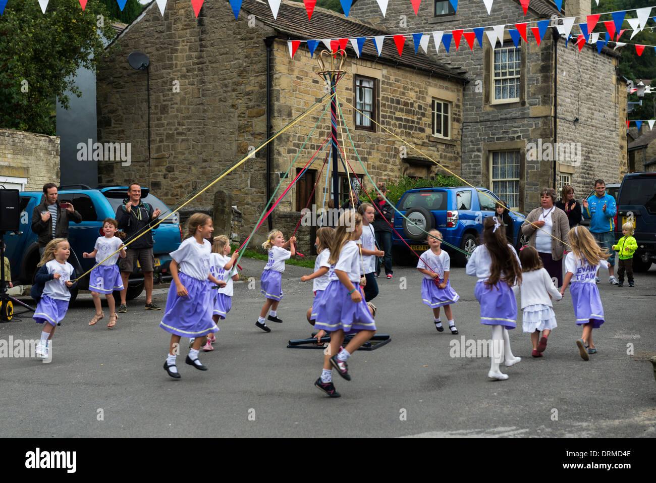 Junge Schüler/Mädchen tanzen um einen Maibaum während Fasnachtswoche in Derbyshire Dorf Eyam Peak District Englands Stockbild