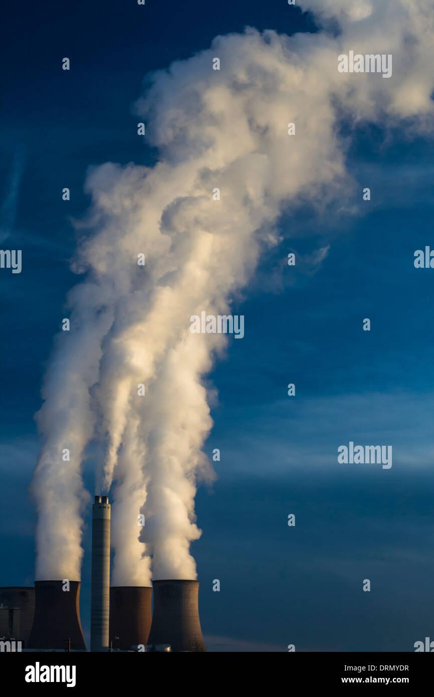 Einen dramatischen Blick auf die Kühltürme eines Kraftwerks mit voller Leistung, wogenden hohe Rauchwolken in einem klaren blauen Himmel. Stockbild