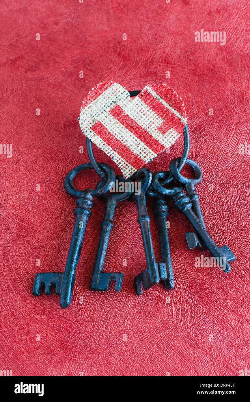 Alten Schlüsselbund auf einem roten Hintergrund, Herzen Leinen Stockbild