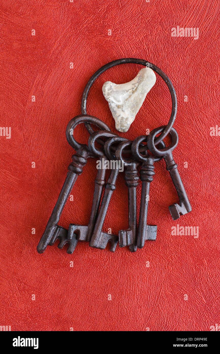 Alten Schlüsselbund auf einem roten Hintergrund, Herz aus Stein Stockbild
