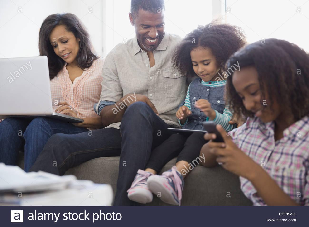 Familie mit drahtlosen Geräten zu Hause Stockbild