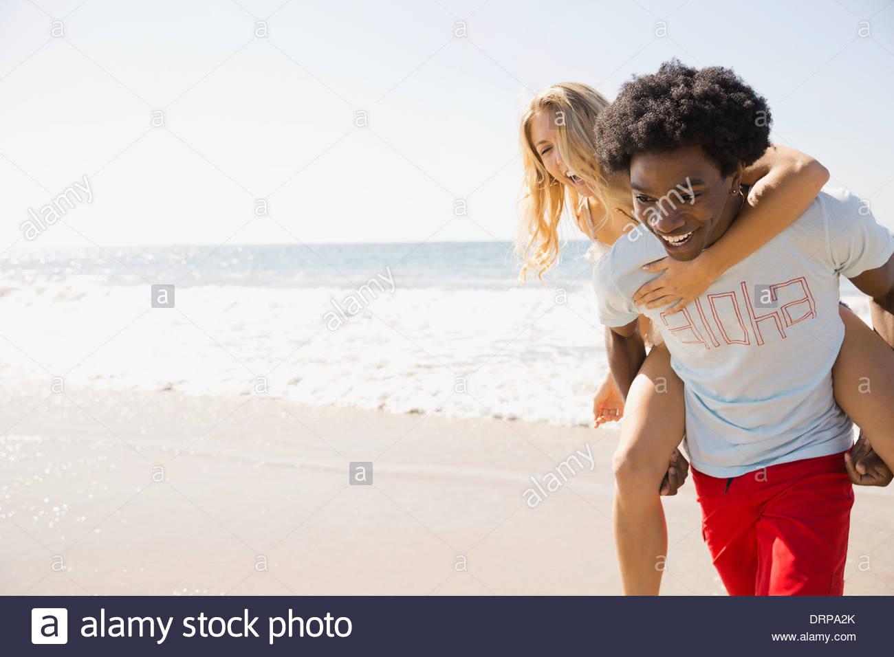 Verspieltes paar am Strand Stockbild