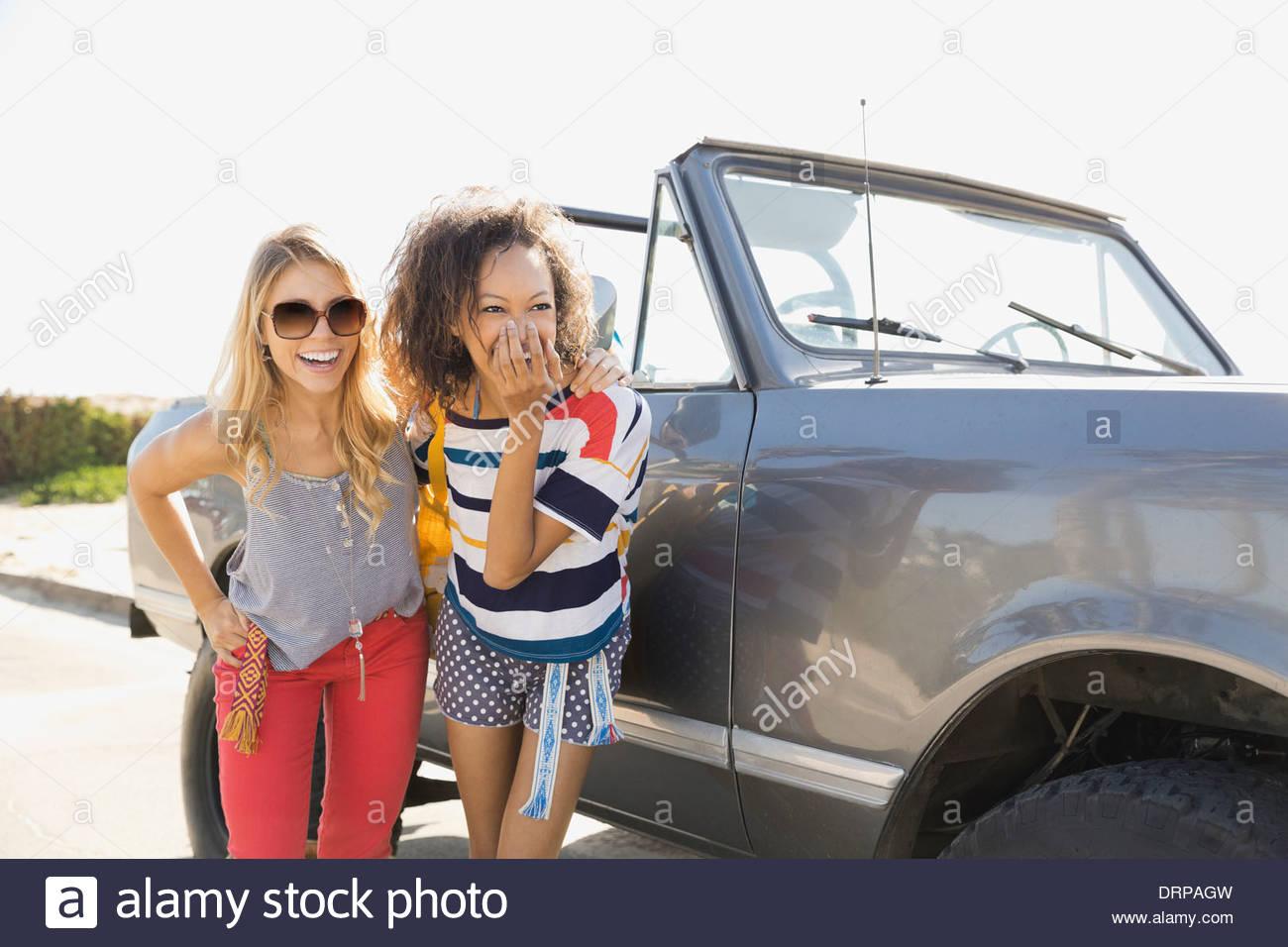 Fröhliche Freundinnen stehend mit einem Off-Road-Fahrzeug Stockbild