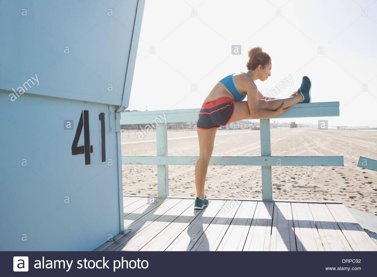 Frau, die Beine vor dem Training zu dehnen Stockbild