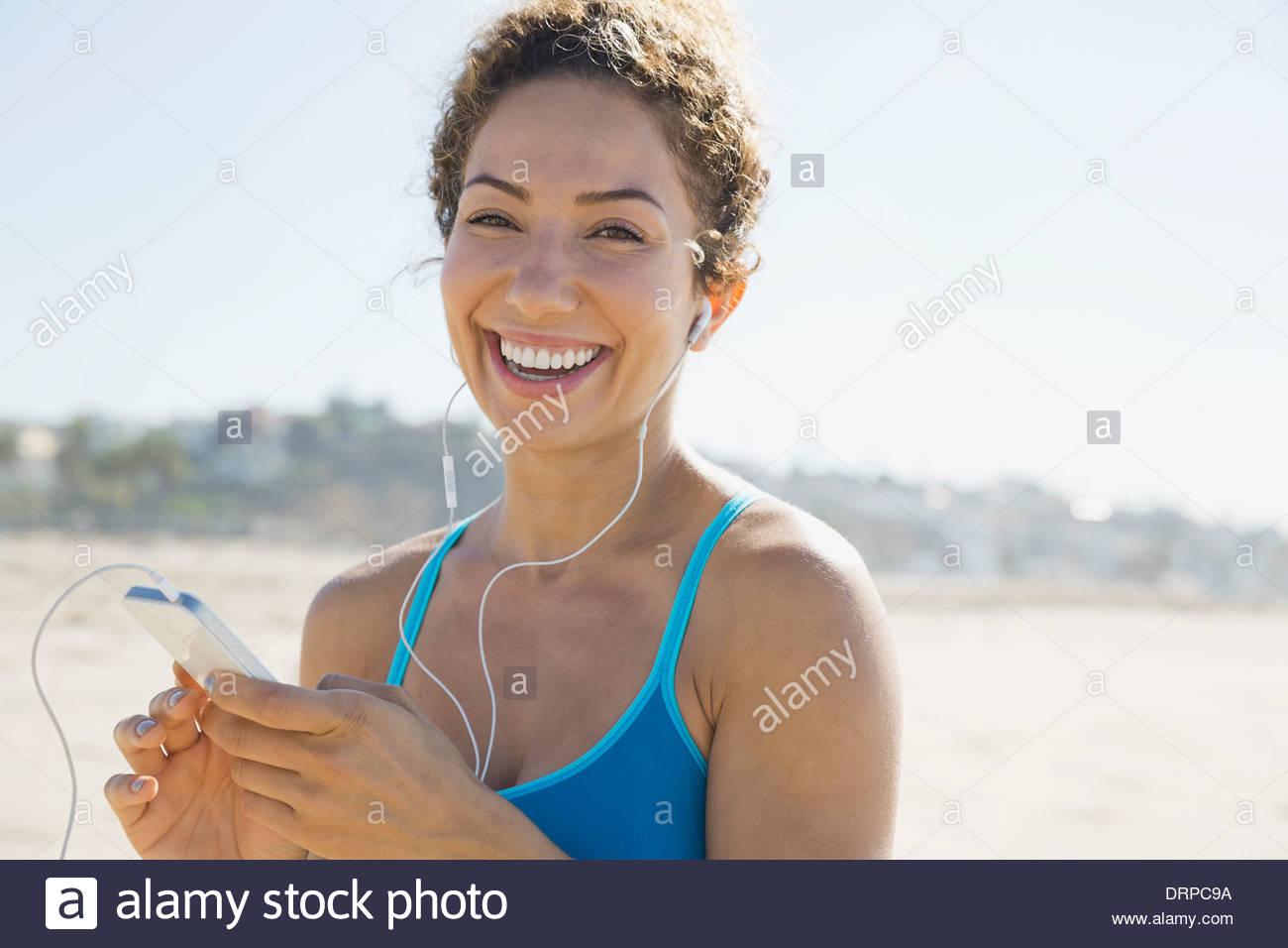 Porträt von aktive Frau anhören von Musik am Strand Stockbild