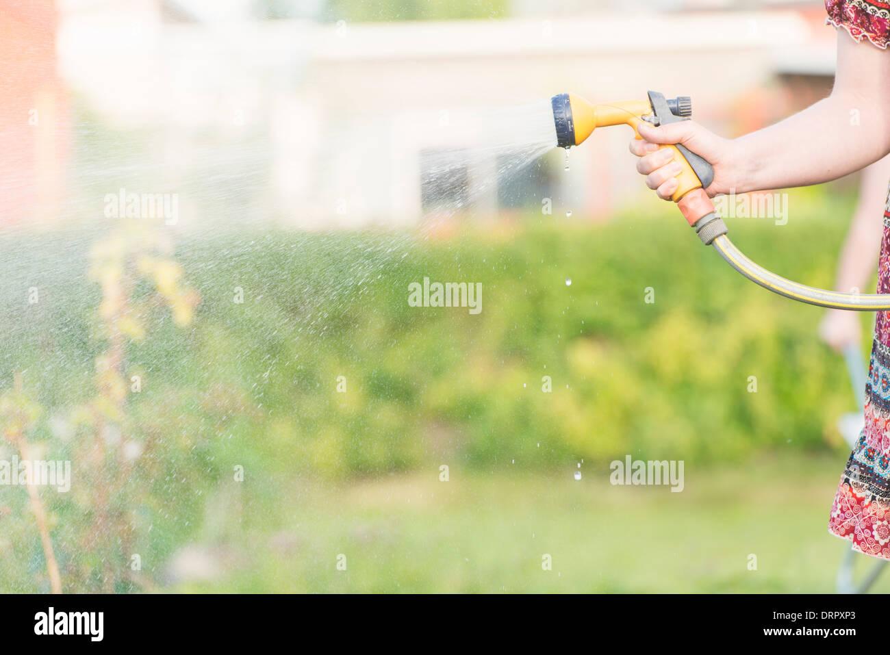 Lifestyle Sommer-Szene. Frau mit Sprinkler Garten Pflanzen gießen. Stockbild