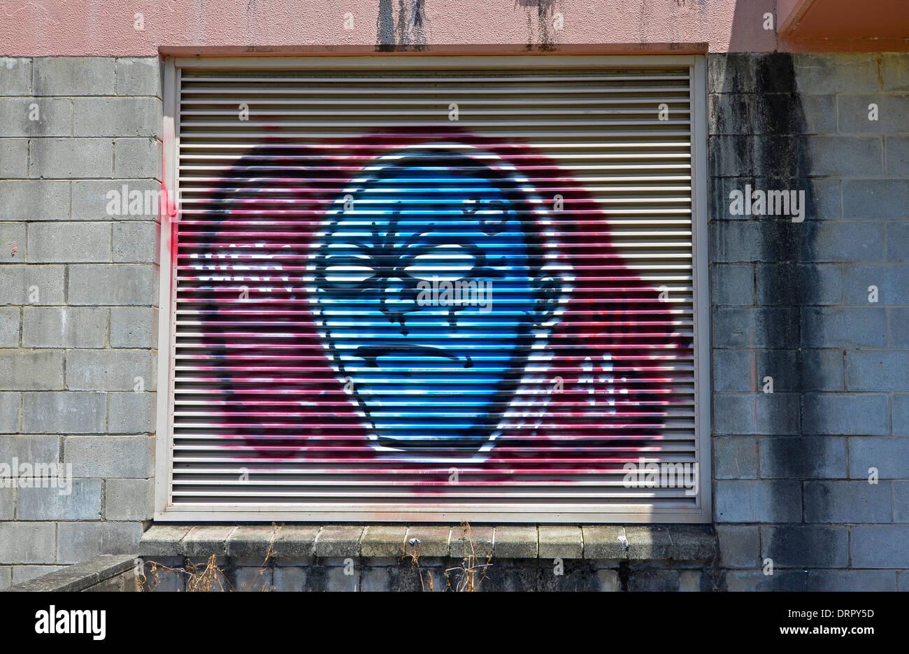 Graffiti von finsteren Gesicht schaute, auf Garagentor Stockbild