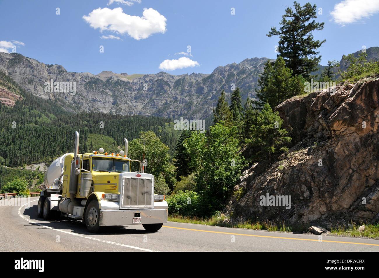 Große gelbe Lastwagen und Rigg klettern die kurvenreiche Landstraße aber die Rockies mit blauem Himmel und Berglandschaft Stockbild