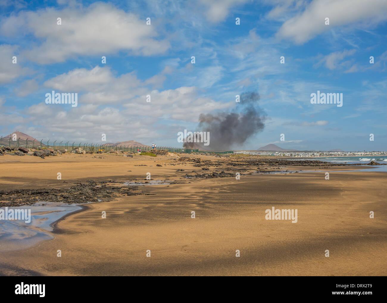 Feuer und Rauch am Start-und Landebahn von Lanzarote Flughafen nahe dem Ozean Stockbild