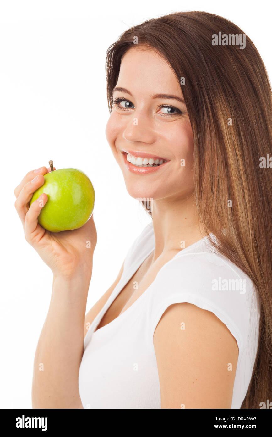 Schöne junge Frau, die einen grünen Apfel, isoliert auf weiss Essen Stockbild