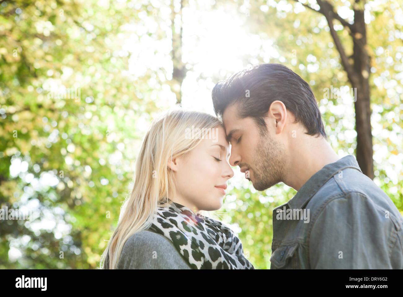 Paar kuschelte mit Augen geschlossen im freien Stockbild