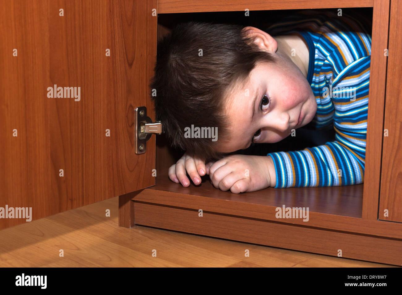 Angst Kind junge versteckt sich im Kleiderschrank Stockfoto