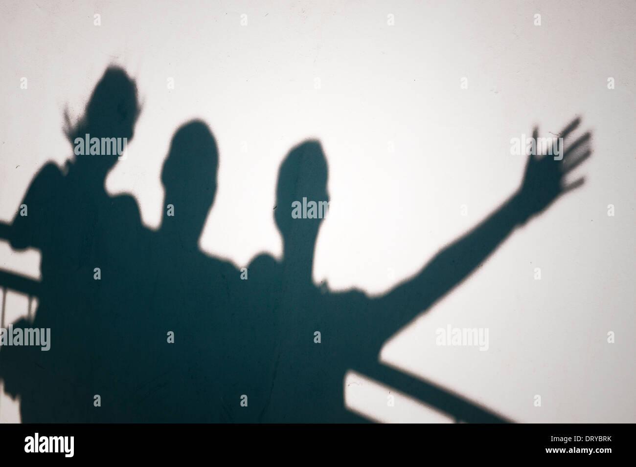 Kreatives Foto von drei Personen Schatten auf die weiße Wand zu gestikulieren Stockbild