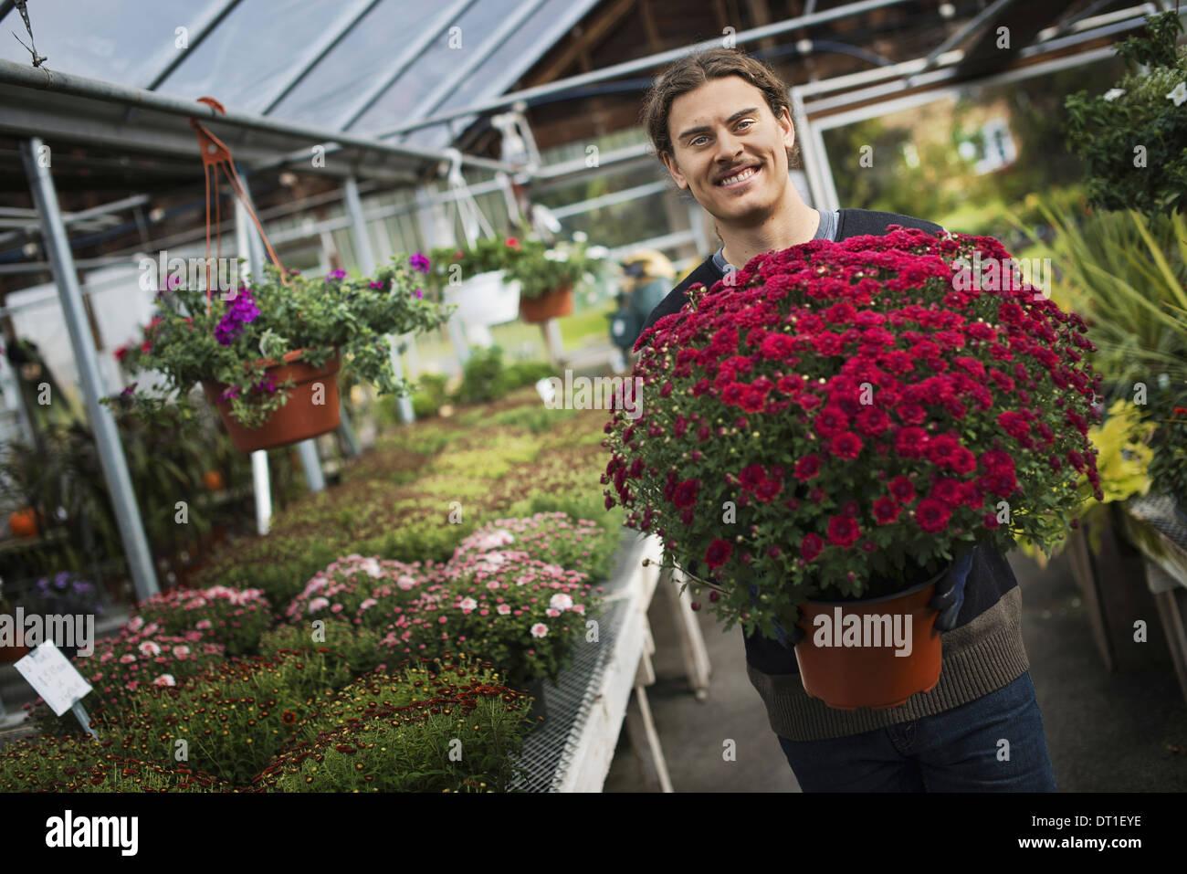 Junger landwirt bei der arbeit  Bio-Landwirt auf Arbeit A junger Mann hält einen großen Topf mit ...