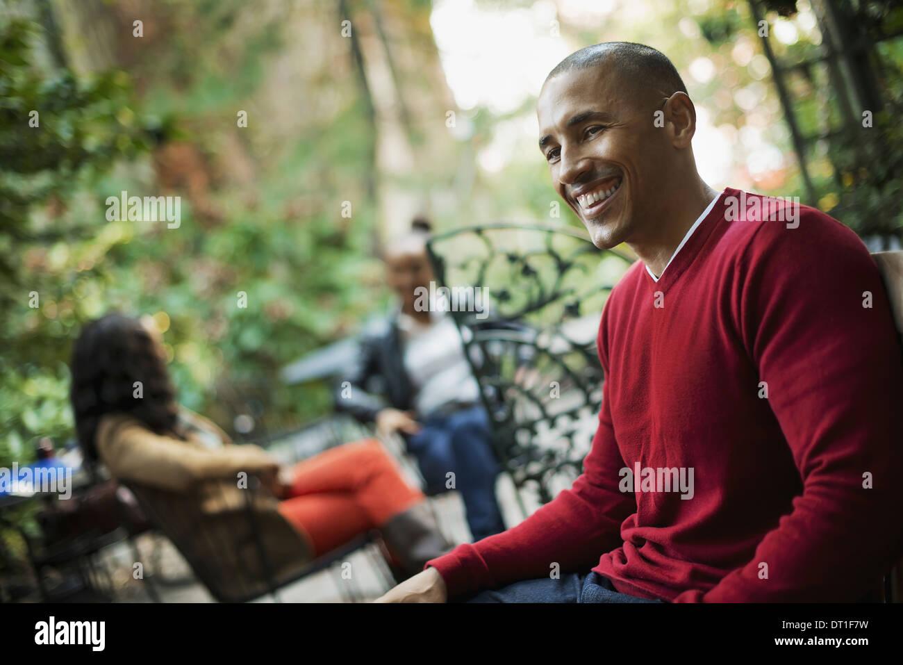 Szenen aus dem städtischen Leben in New York City drei Leute sitzen in einem Platz im freien Mann Frau und Stockbild