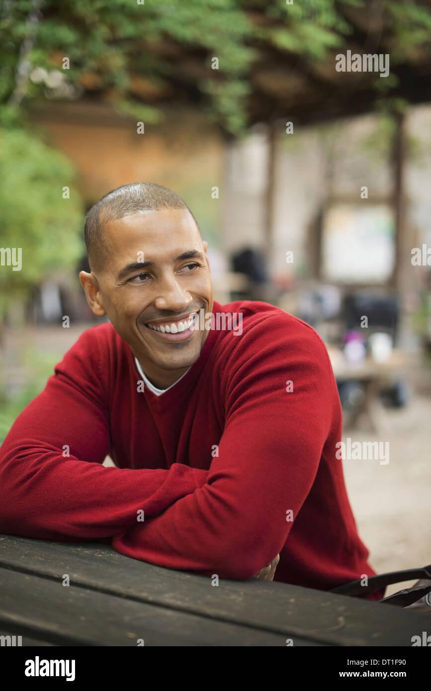 Szenen aus dem städtischen Leben in New York City ein Mann in einem roten Jumper sitzt auf einer Bank lächelnd Stockbild