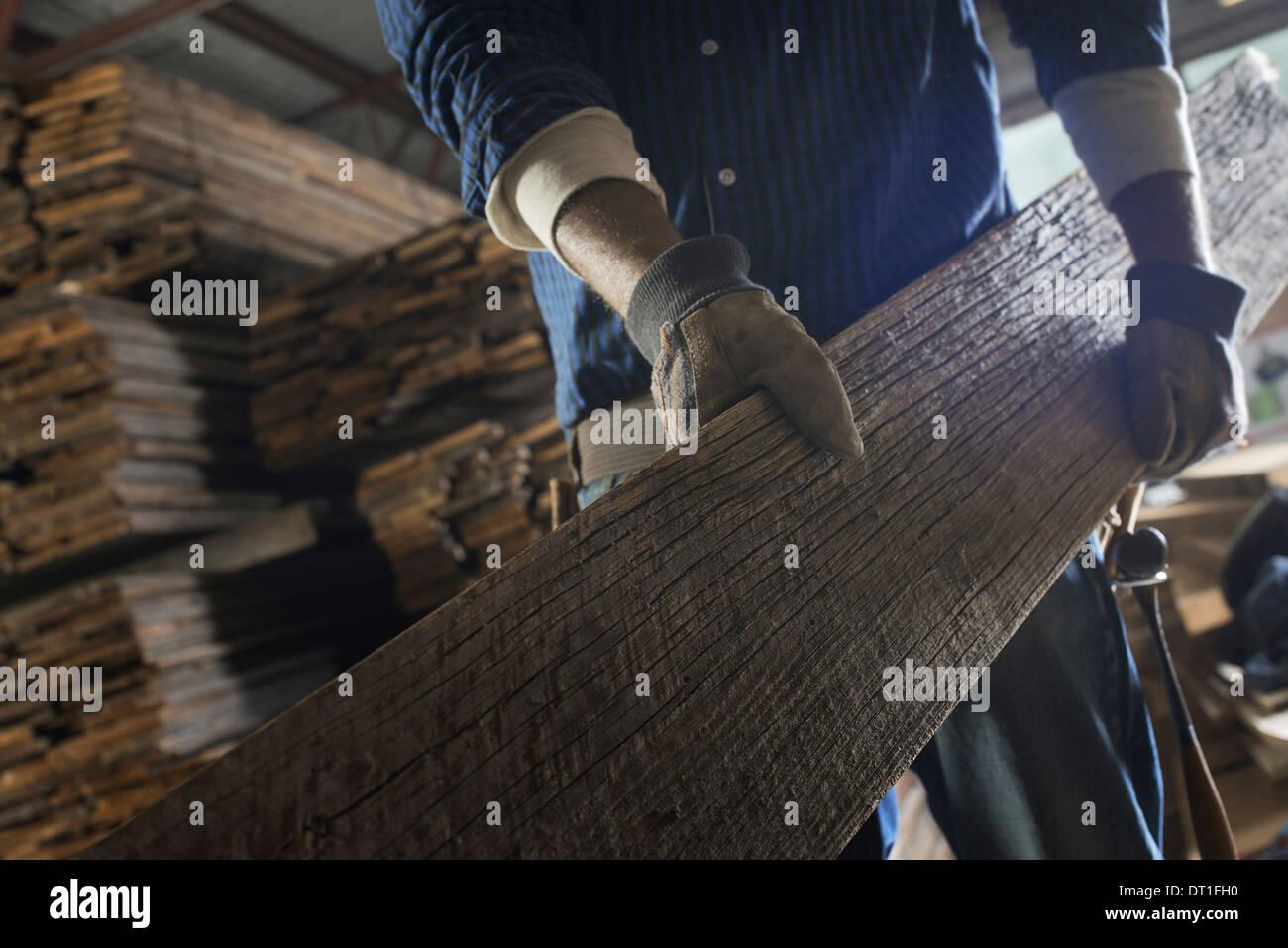 Ein Haufen von recycelten aufgearbeiteten Holz Holzplatten in einem Holz Hof einen Mann mit einem großen Brett Stockbild