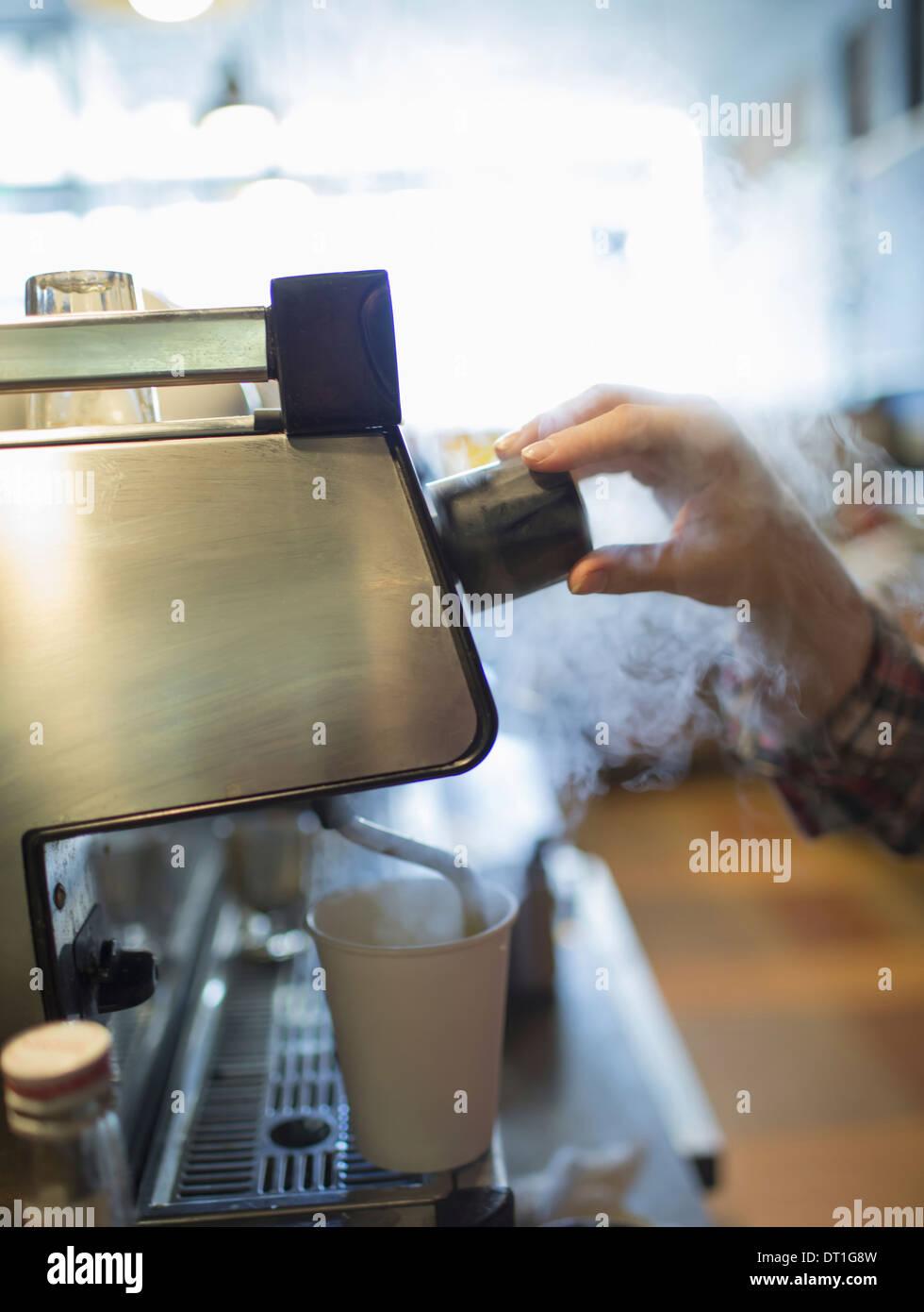 Eine Person Barista Kaffee kochen und Aufschäumen von Milch mit einem Dampf-Rohr-Coffee-shop Stockbild
