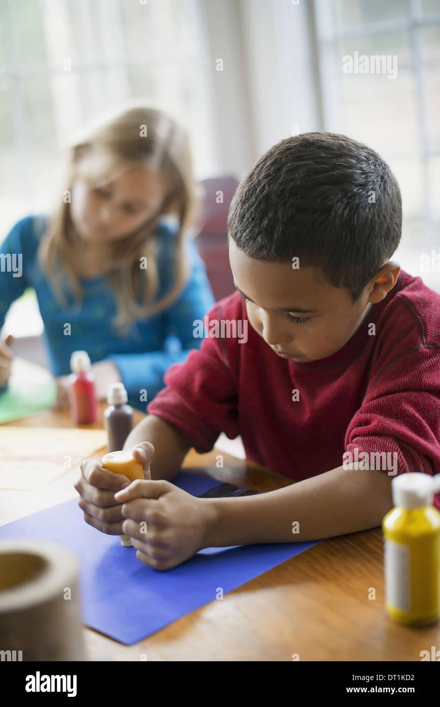 Kinder in einer Familie zu Hause zwei Kinder sitzen am Tisch mit Farbe und Papier Dekorationen erstellen Stockbild