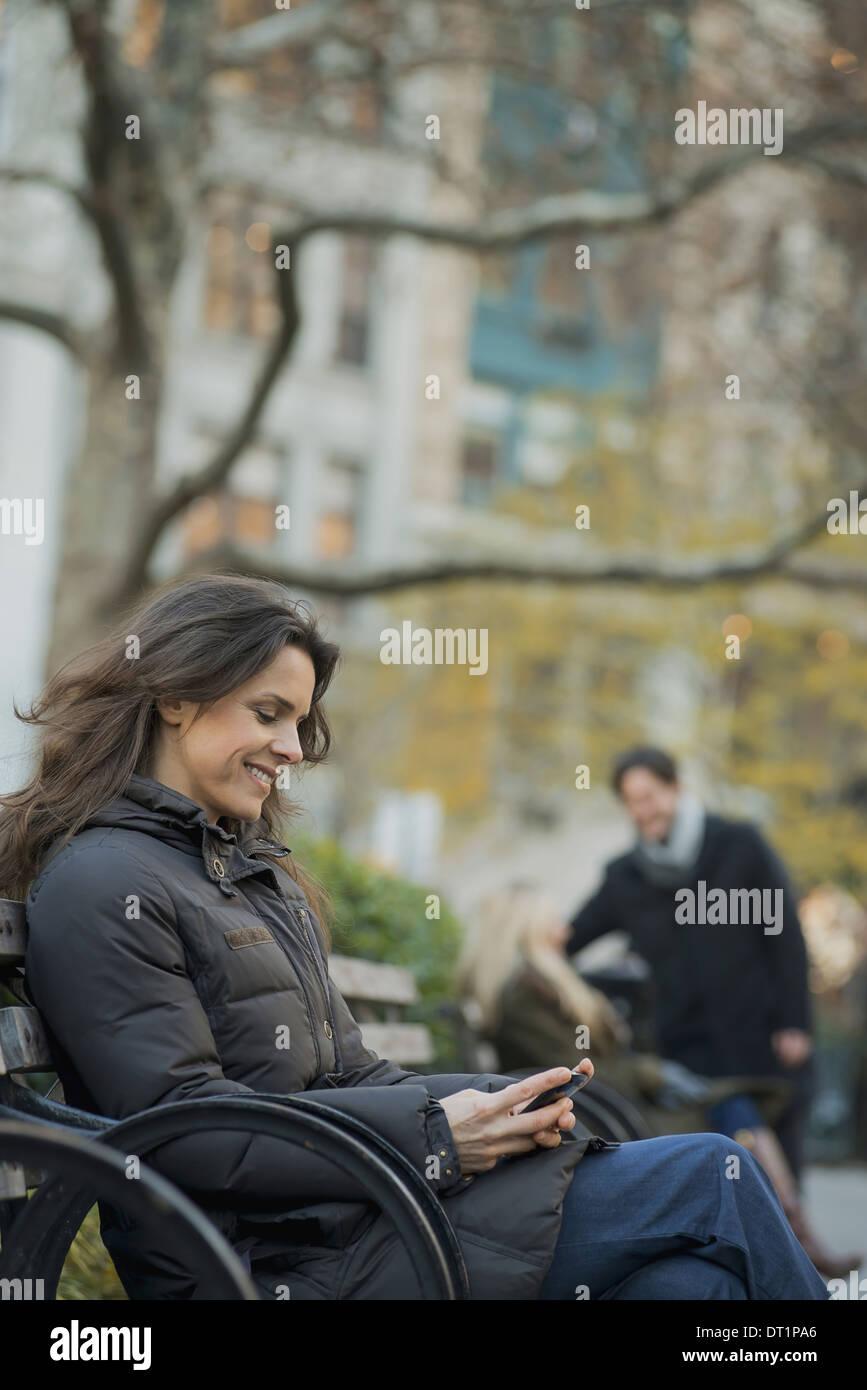 Frau sitzend im Stadtpark mit smartphone Stockbild