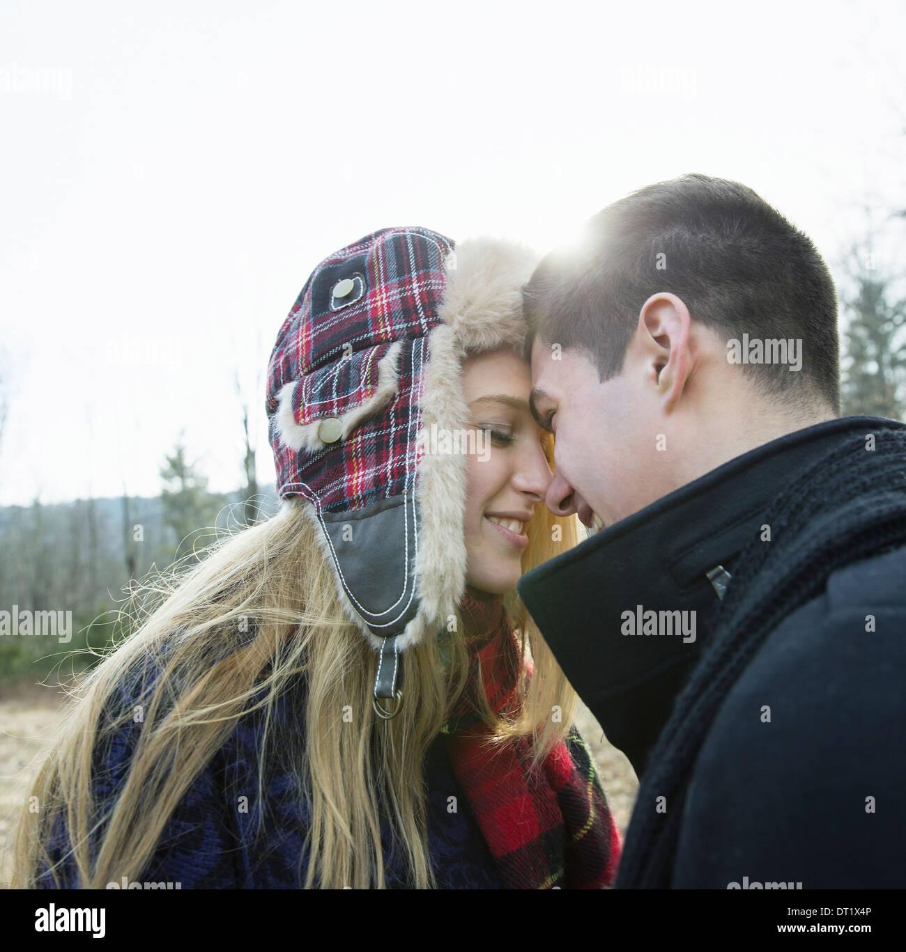 Ein paar junge Mann und Frau umarmt von Angesicht zu Angesicht im Freien an einem kalten Wintertag Stockbild