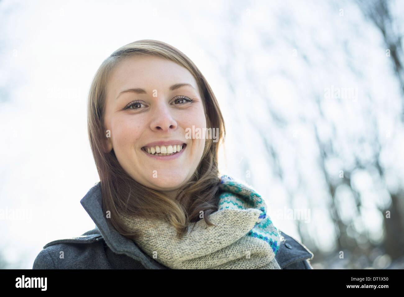 Eine junge Frau in einem Schal und Mantel außerhalb an einem Wintertag Stockfoto
