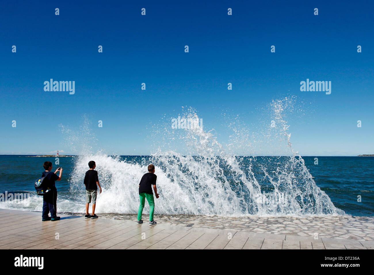 Drei Jungs auf dem Kai während eine Welle auf sie zu brechen Stockbild