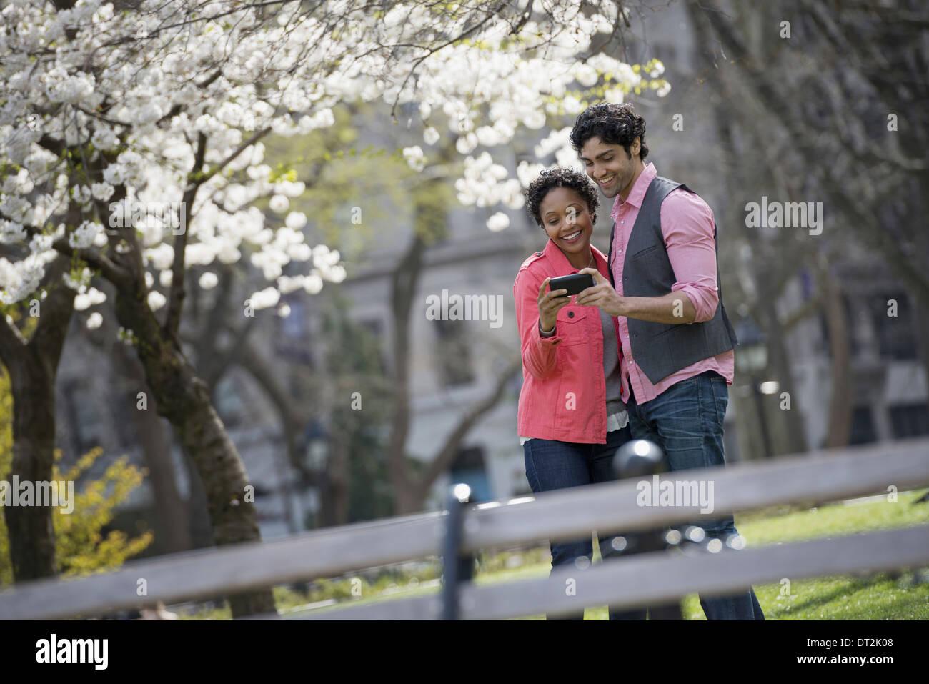 New York City Park A Mann und Frau nebeneinander mit dem Fotografieren mit einer Hand statt Handy Stockbild