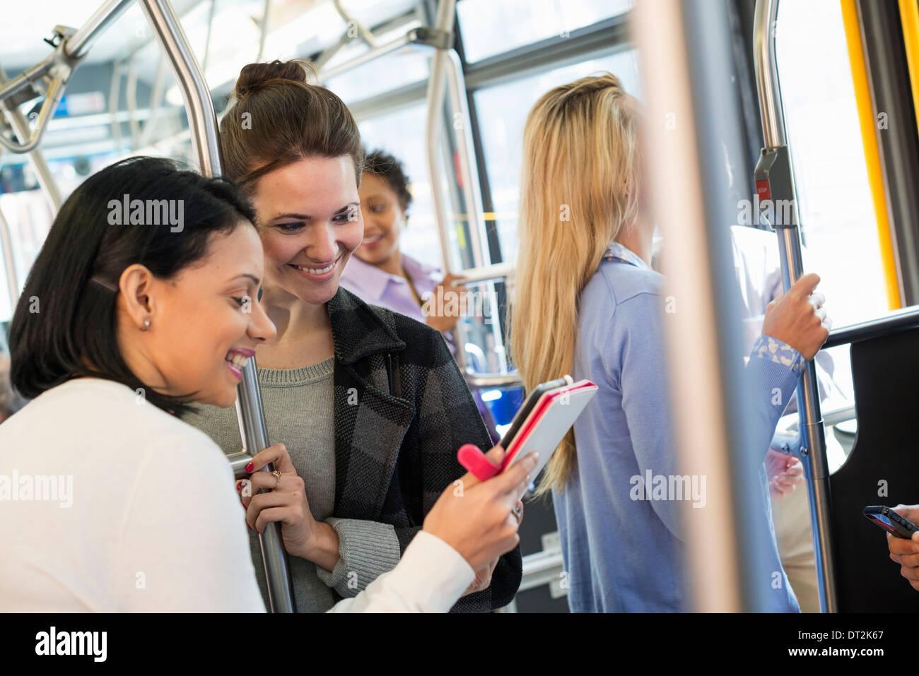 New York City Menschen-Männer und Frauen auf einem Stadtbus ÖPNV zwei Frauen, die mit einem handheld digital tablet Stockbild