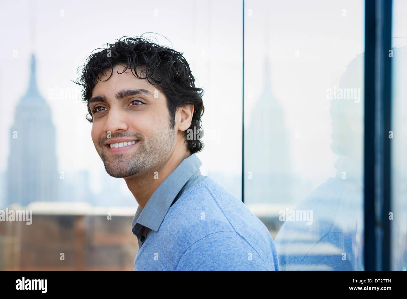 Urban Lifestyle A junger Mann mit schwarzen lockigen Haaren trug ein blaues Hemd in der Lobby eines Gebäudes Stockbild