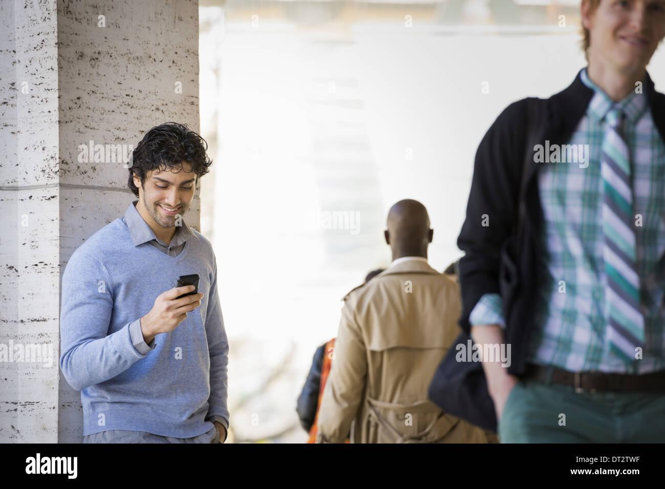 Drei Menschen auf dem Bürgersteig ein Mann mit seinem Handy ein Mann im Regenmantel und ein junger Mann auf der Straße Stockbild