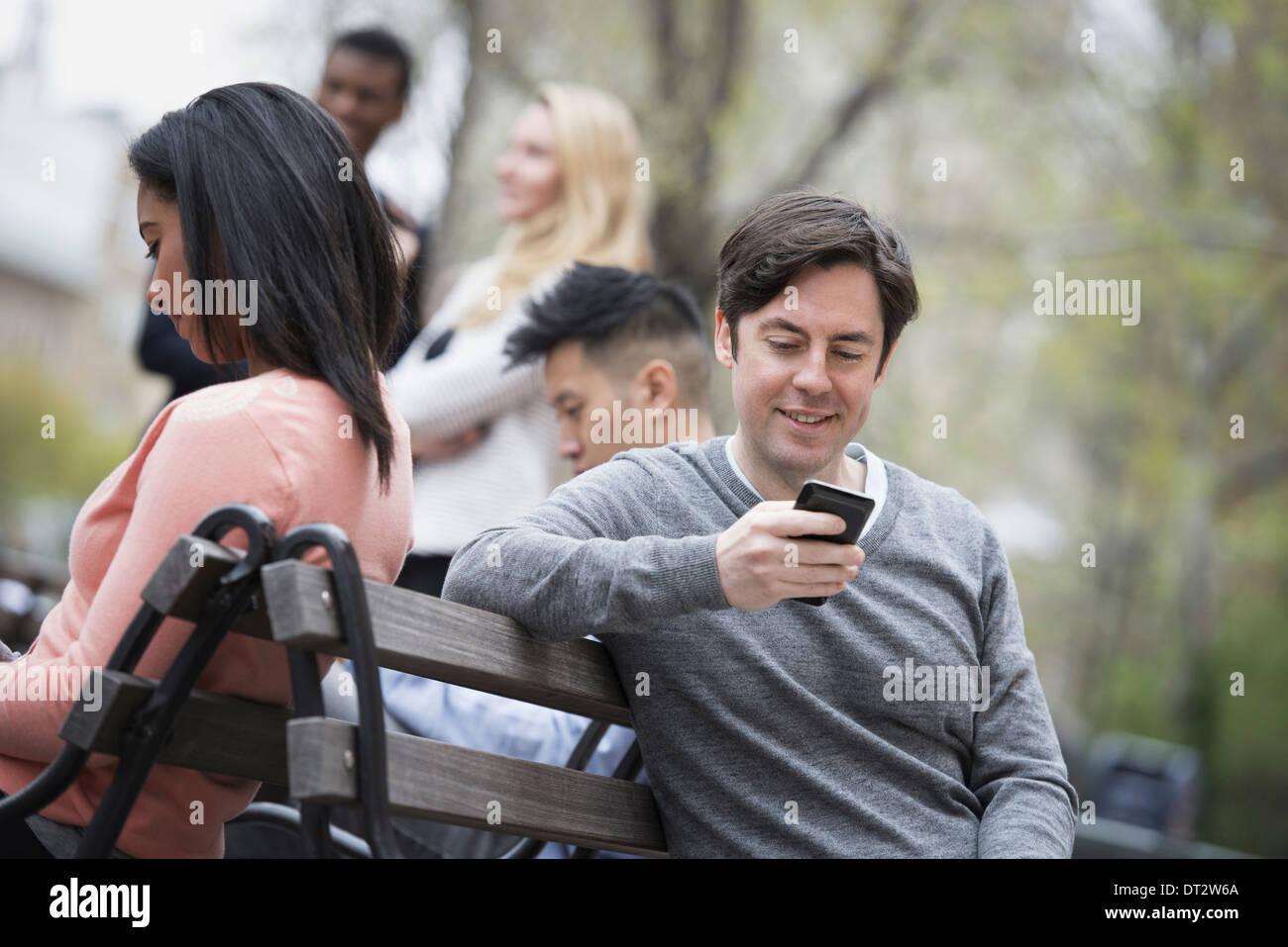 Blick über Citycity Park auf einer Parkbank sitzen, fünf Menschen Männer und Frauen, die ihre Telefone überprüfen Stockbild