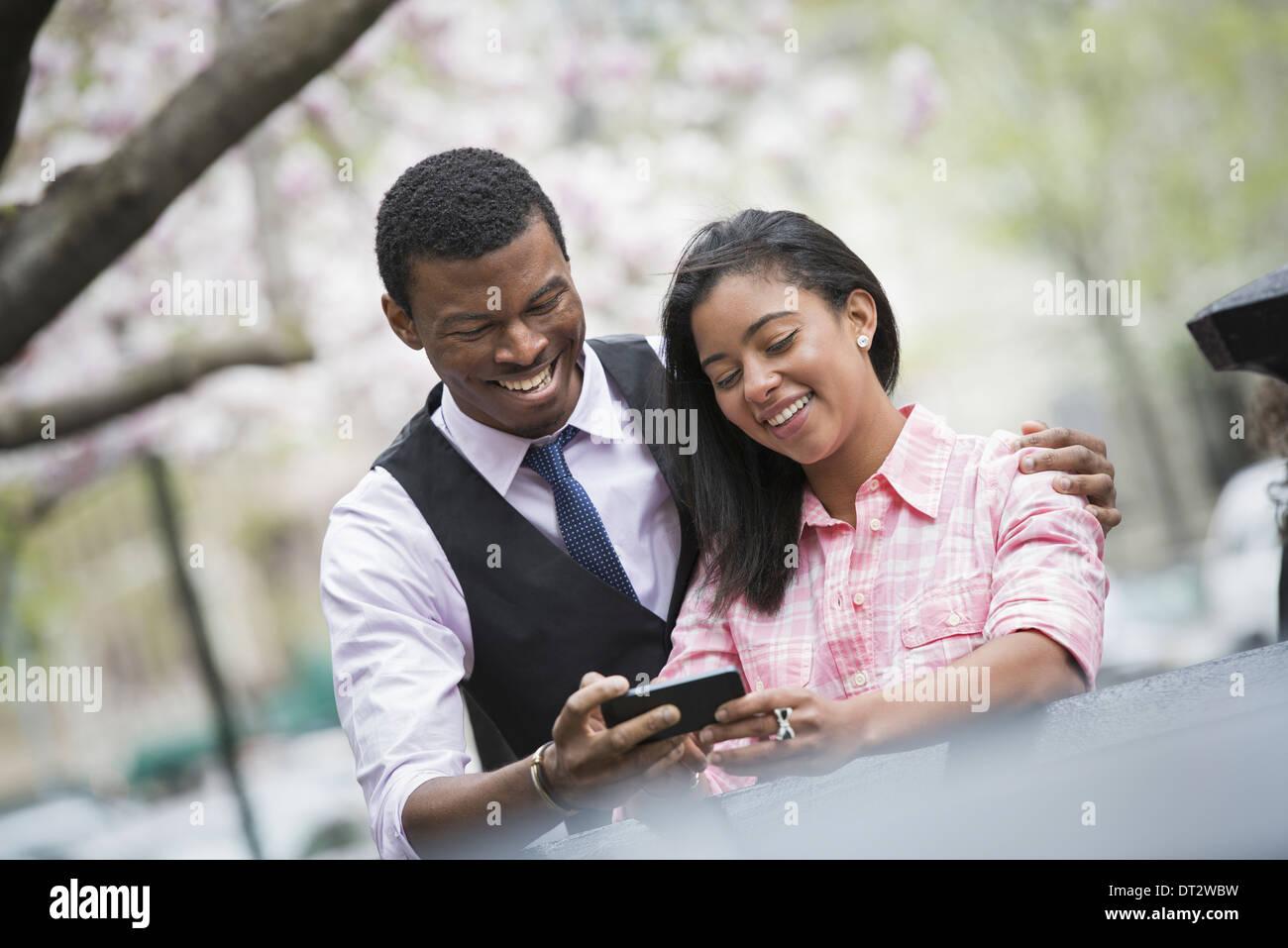 Blick über CityYoung Menschen ein paar Seite an Seite mit seinen Arm um ihre Schultern mit Blick auf ein Smartphone und lächelnd Stockbild