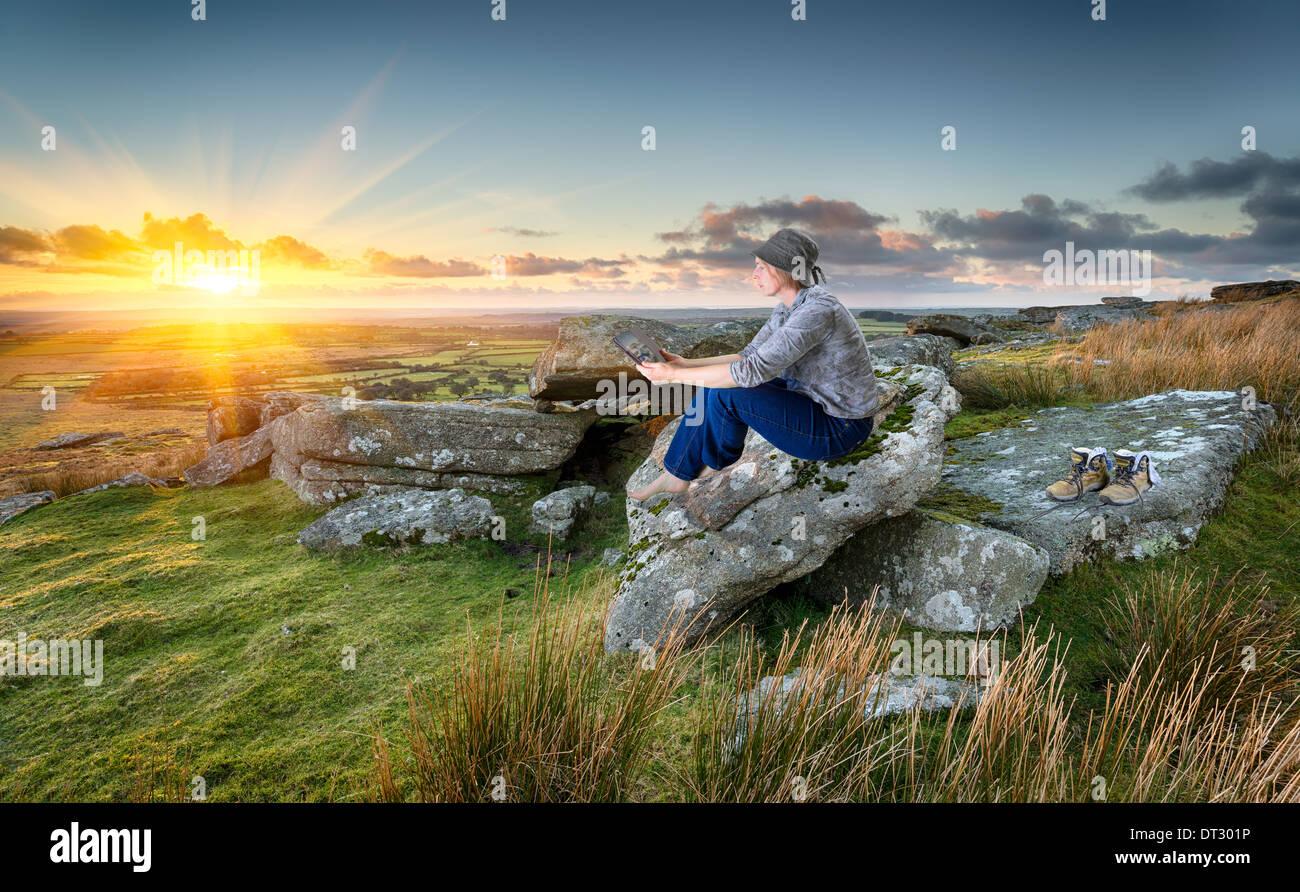 Frau, Wandern, entspannen und unter Verwendung eines Tablet PCs bei Sonnenuntergang auf einem felsigen Tor auf Bodmin Moor in Cornwall Stockbild