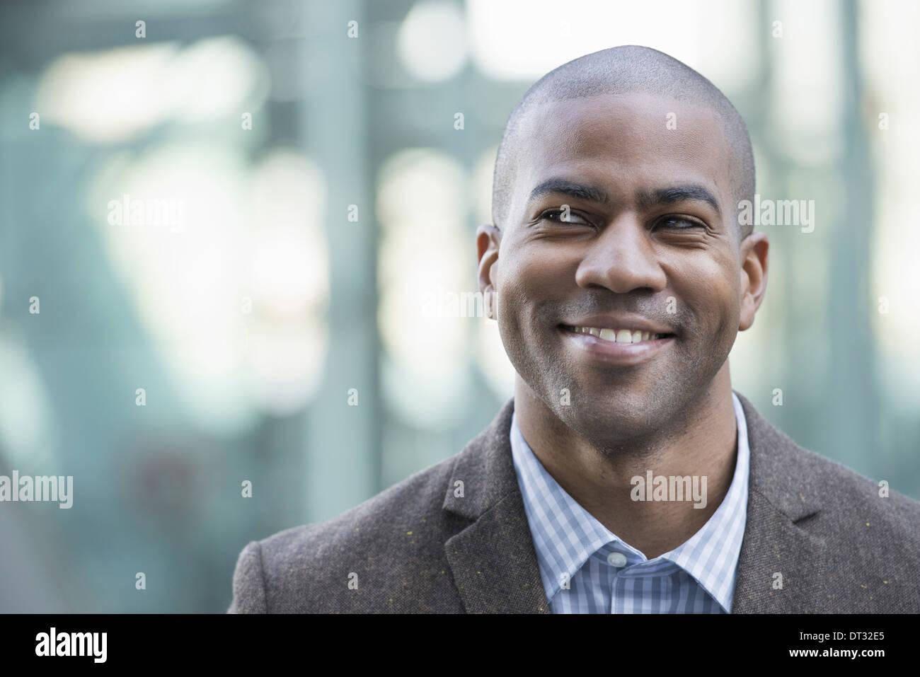 Ein Mann in Anzug und Krawatte lächelnd und Blick in die Ferne Stockbild