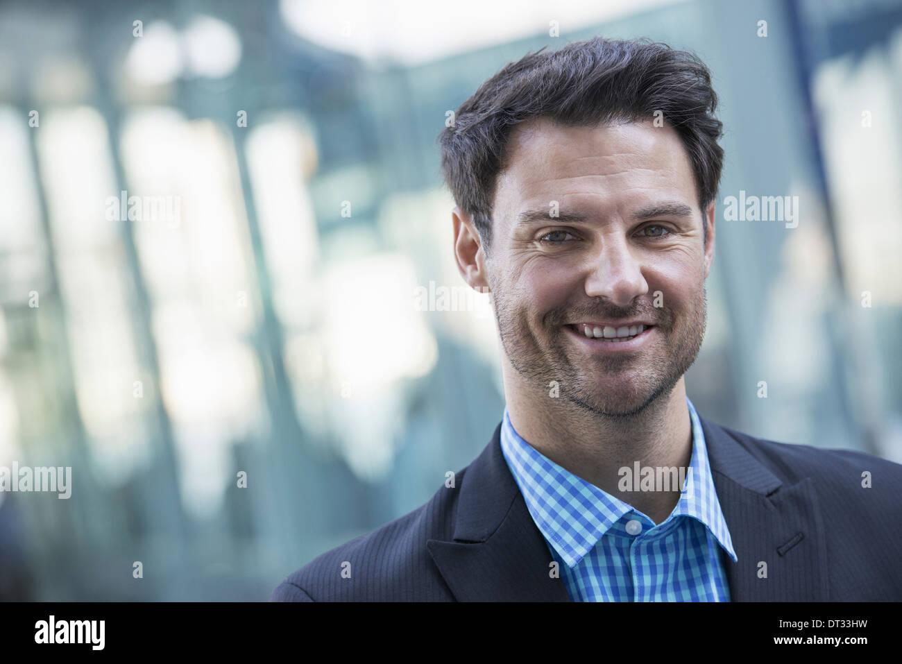 Ein Mann in ein blaues Hemd und dunkle Jacke lächelnd Stockbild