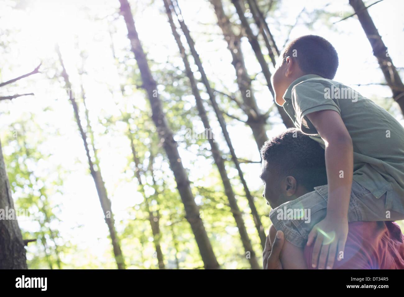 Ein Junge sitzt auf seines Vaters Schultern Stockbild