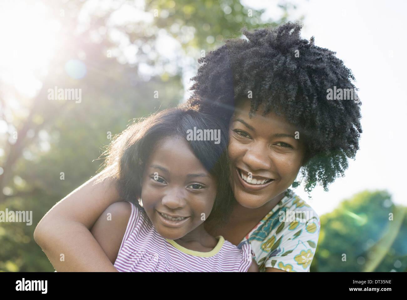 Eine junge Frau und ein Kind umarmen Stockbild